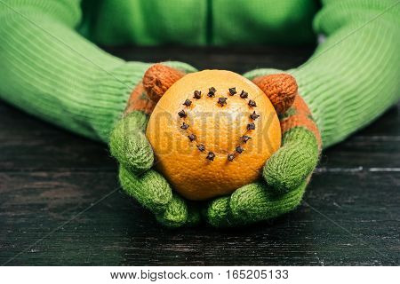 Female hands in bright-colored gloves giving heart-shaped pomander to the viewer. Overhead view