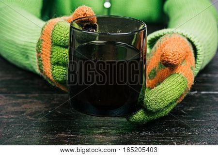 Human hands in bright-colored winter gloves giving big mug of tea to the viewer. Front view