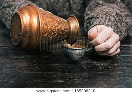 Human hands pouring coffee from copper pot to metal cup. Front view