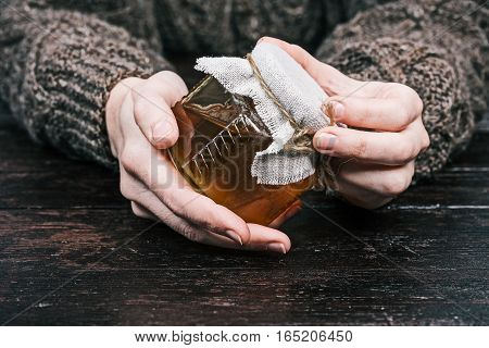 Human hands holding closed little glass can of honey. Front view