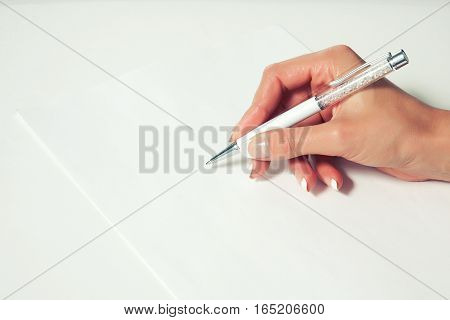 Elegant female hand with French manicure writes beautiful pen on a blank sheet