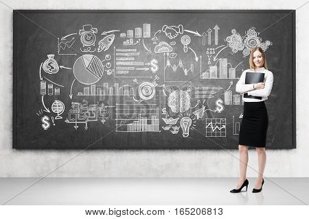 Blond woman with a folder is standing near a blackboard with white start up sketches depicted on it. Concept of small business