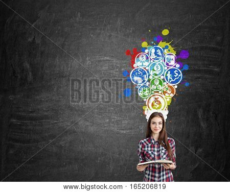 Portrait of a young woman wearing a checkered shirt and holding a book. She is standing near a blackboard with colorful business icons forming a light bulb. Mock up