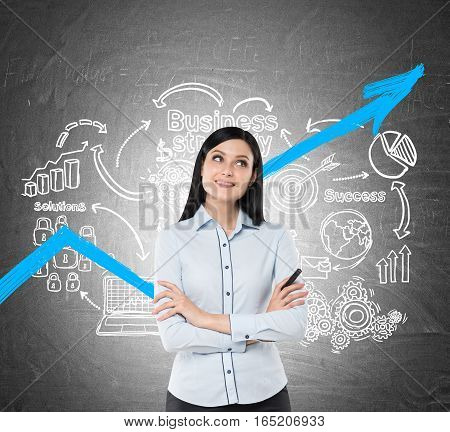 Portrait of an inspired businesswoman with black hair and a marker. She is standing near a blackboard with a blue growing graph and business strategy icons on it.