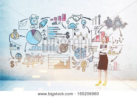 Blond woman with a folder is standing near a concrete wall with colorful start up sketches depicted on it. Concept of small business. Toned image