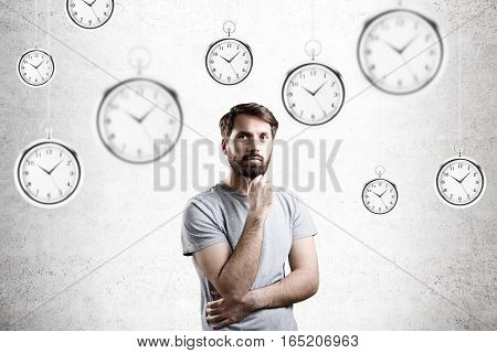 Bearded man in a gray T-shirt is standing and thinking in a room with hanging giant pocket watches. Concrete background.