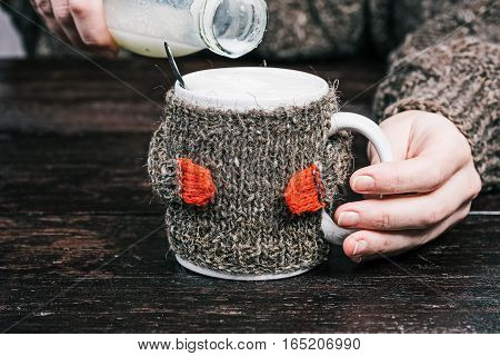 Human hands holding mug of milk in wool warmer. Front view