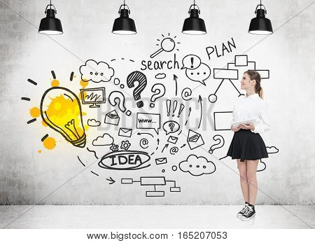 Young girl in a white blouse and a black skirt is standing with her tablet computer near a concrete wall with a bright light bulb and business plan sketches. 3d rendering