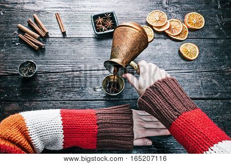 Female hands pouring black coffee from coffee pot to little cup. Overhead view