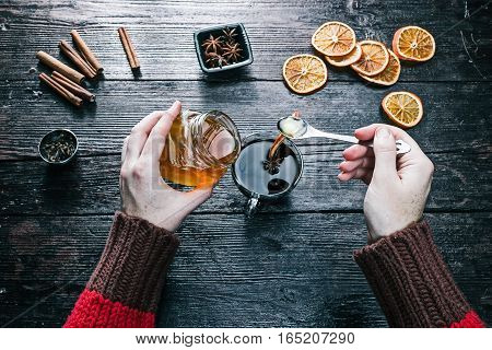 Female hands holding a jar of honey and putting it to the cup of tea. Overhead view