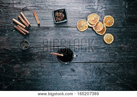 Tea cup, cinnamon sticks, anise stars, dried oranges and cloves on the table. Overhead view