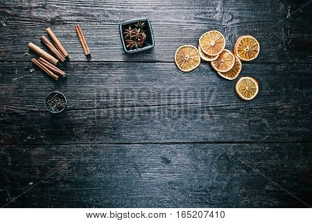 Cinnamon sticks, anise stars, dried oranges and cloves on the table. Overhead view