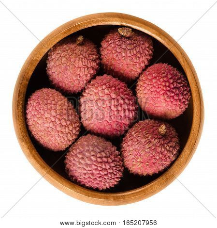 Lychee or litchi fruits in wooden bowl. Unpeeled ripe red Litchi chinensis, also called liechee, liche, lizhi or li zhi. Isolated macro food photo close up from above on white background.