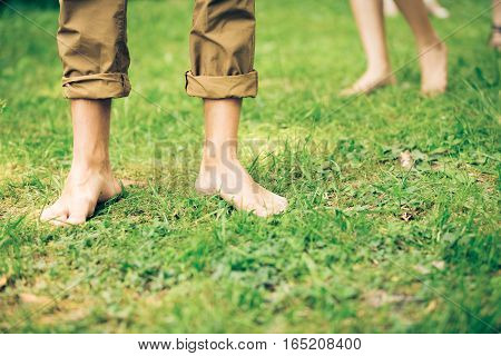 young people walking barefoot in the grass.
