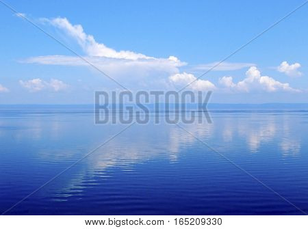 Cloudscape big white cloud and reflection in water clouds over lake Baikal Russia