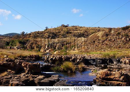 small mountain river under a blu sky and among orange hills and rocks