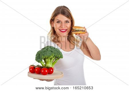 Picture of a beautiful woman holding a hamburger and fresh vegetables