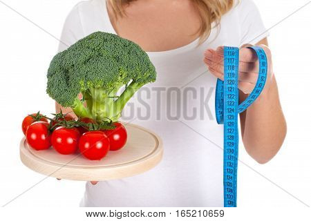 Picture of fresh vegetables and measurer held by a woman