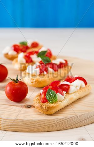 Italian crostini with mozzarella cherry tomatoes and basil over a chopping board and blue background