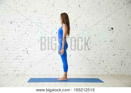 Young happy attractive woman practicing yoga, standing in mountain exercise, Tadasana pose, working out, wearing sportswear, blue suit, indoor full length, white loft studio background. Side view