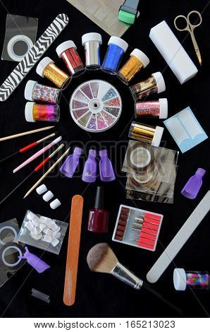 Tools for manicure and a multi-colored foil for nail decoration, the procedure in the beauty salon