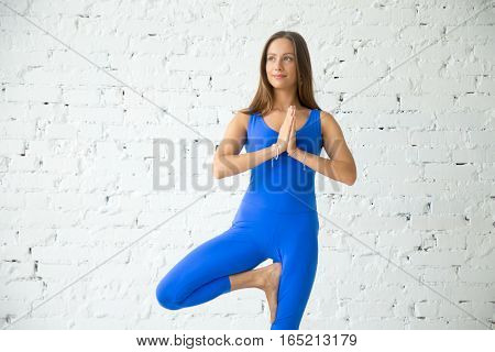 Portrait of young attractive smiling woman practicing yoga, standing in Vrksasana exercise, Tree pose with Namaste, working out, wearing sportswear, blue suit, indoor, white loft studio background
