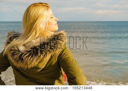 Leisure spending free time outside healthy walks concept. Woman wearing warm jacket relaxing on beach near sea cold sunny day back view