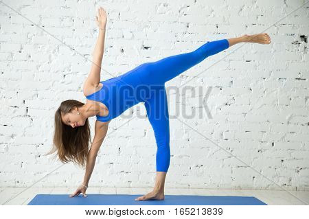 Young attractive smiling woman practicing yoga, standing in Half Moon exercise, Ardha Chandrasana pose, working out, wearing sportswear, blue suit, indoor full length, white loft studio background