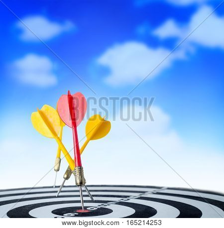 Close up shot red dart arrow on center of dartboard and yellow arrow not hit the target on blue sky background metaphor to target success