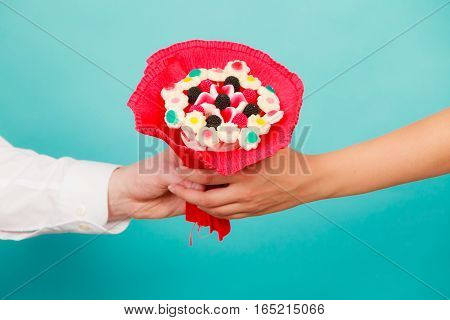 Closeup of man giving woman candy bunch flowers. Boyfriend holding present gift for girlfriend. Love.