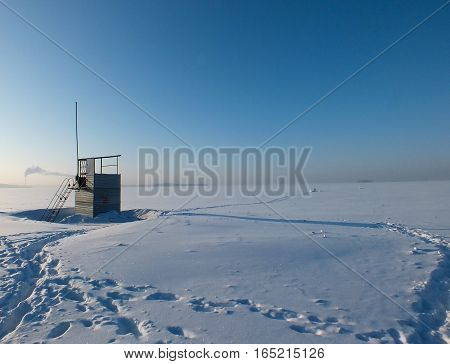 Lifeguard tower on the beach of frozen sea covered in snow