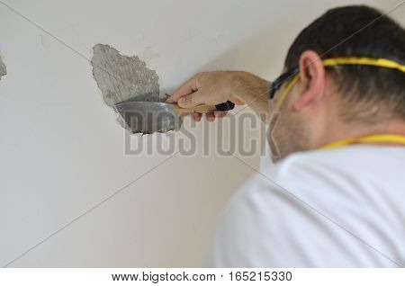 Man peeling a ceiling with a plaster spatula