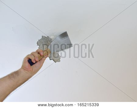 Scraping A Ceiling With A Spatula