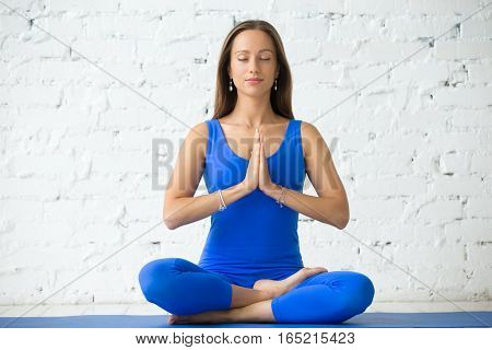 Young attractive woman practicing yoga, sitting in Half Lotus exercise, Ardha Padmasana pose, working out, wearing sportswear, blue suit, full length, white studio background, closed eyes, Namaste
