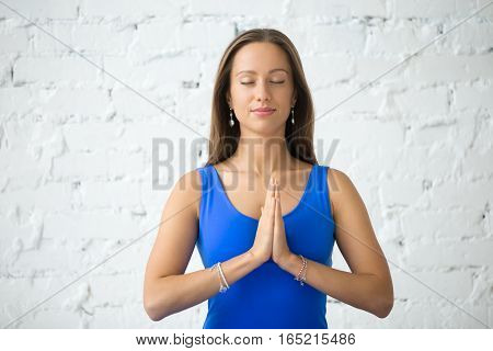 Portrait of smiling attractive woman practicing yoga, in Namaste pose, working out, wearing sportswear, blue tank top, indoor, white loft studio background, closed eyes on meditation session