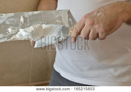 Preparing spackling compound with a finishing trowel and spatula before applying on a wall