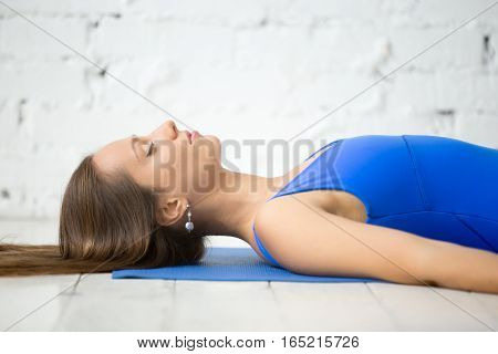 Young attractive woman practicing yoga, lying in Dead Body, Corpse exercise, Savasana pose, working out wearing sportswear, blue tank top, indoor, white loft studio background