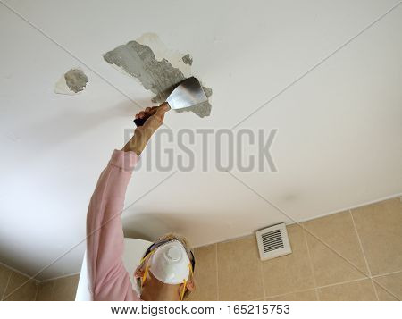 Woman with protecting mask holding a plaster spatulapeeling a ceiling preparing it for smoothing