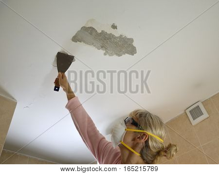 Woman with protecting mask and glasses holding a plaster spatulapeeling a ceiling preparing it for smoothing