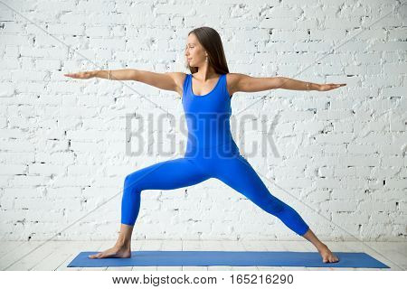 Young attractive woman practicing yoga, standing in Virabhadrasana 2 exercise, Warrior Two pose, working out, wearing sportswear, blue suit, indoor full length, white loft studio background