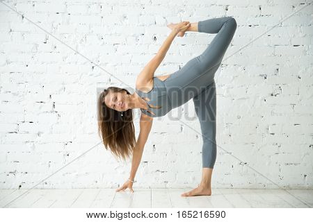 Young attractive smiling woman practicing yoga, standing in Half Moon exercise, Ardha Chandrasana pose, working out, wearing sportswear, grey suit, indoor full length, white loft studio background, looking at the camera