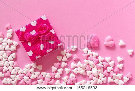rosa und weiße Zuckerherzen und Geschenkpäckchen auf rosa Untergrund zum Geburtstag