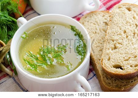 Chicken bouillon with fresh bread in the white bowl.