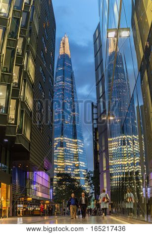 London UK - 4 October 2016:  People walking by London More riverside street ,surrounded  by Modern architecture and the Shard tower in the background