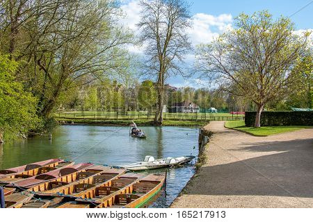 Oxford, UK - April 30, 2016: Turists punting in river Cherwell on a sunny day near univesity of Oxford botanic gardens and Magdalen Bridge