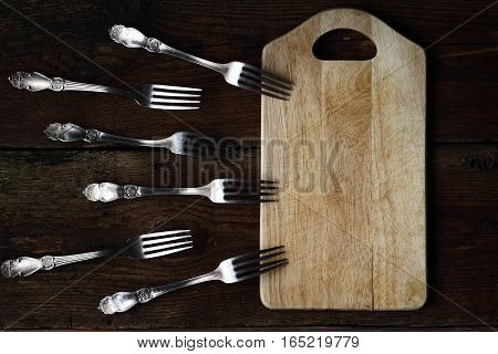 Forks With Kitchen Board On Wooden Background