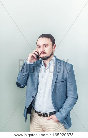 Young man talking on the phone in a denim jacket on gray background.