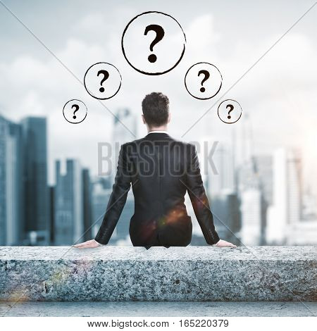 Confused businessman sitting on rooftop with question marks. Confusion concept