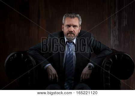 Portrait of a mature businessman in a black suit on dark background