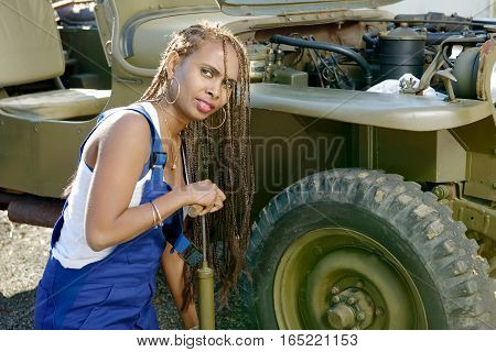 pretty young African American woman mechanic inflates a tire